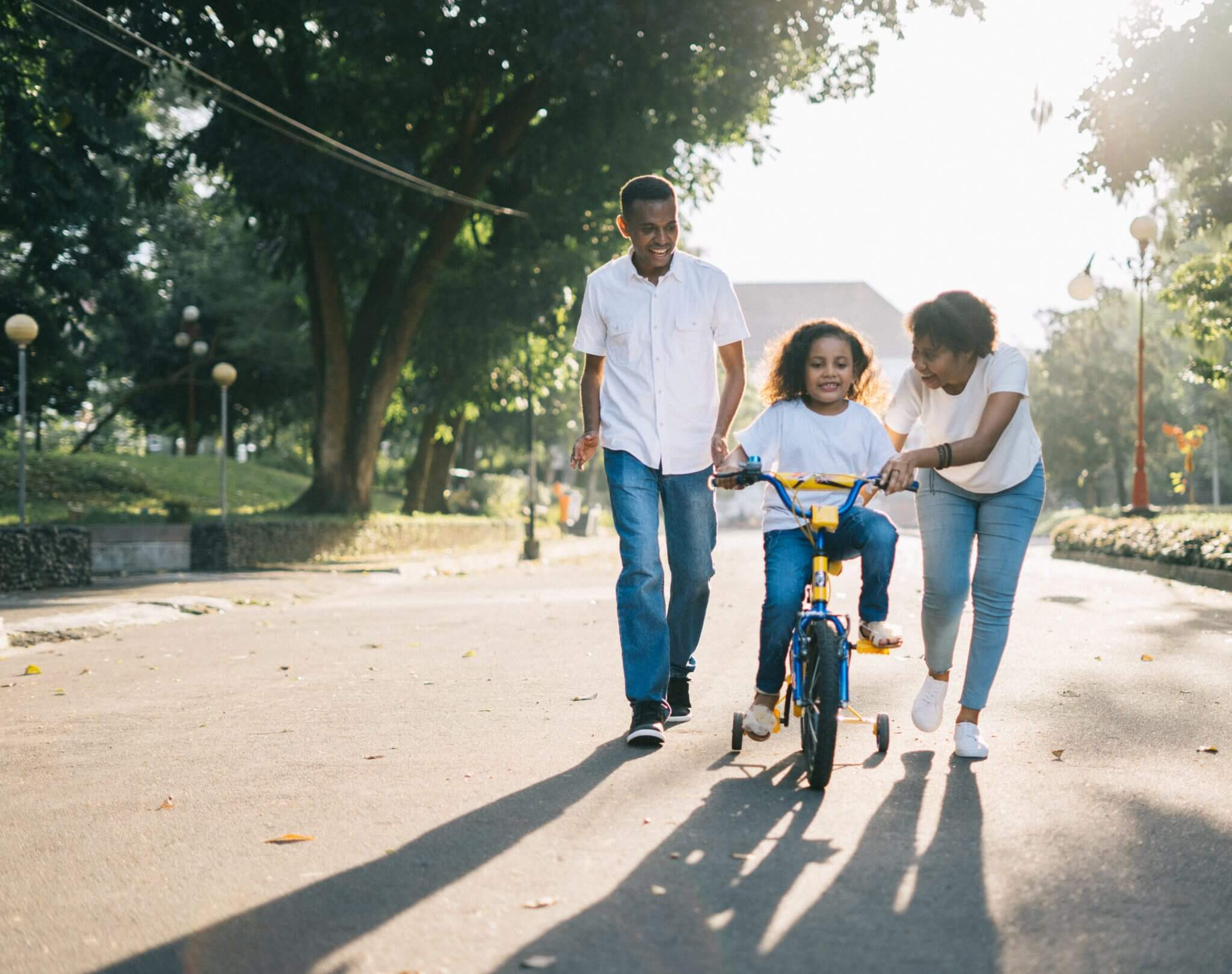 Family learning to ride bike